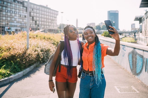 Młodych pięknych czarnych siostr plenerowy podświetlenie używa smartphone bierze selfie