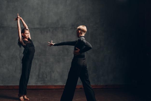 Młodych profesjonalnych tancerzy sportowych tańczących w sali balowej paso doble.