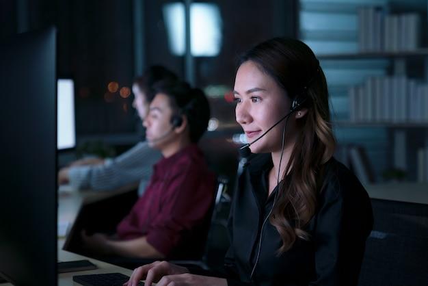 Młodych tajskich azjatyckich operatorów obsługi klienta, pracujących na nocną zmianę w call center