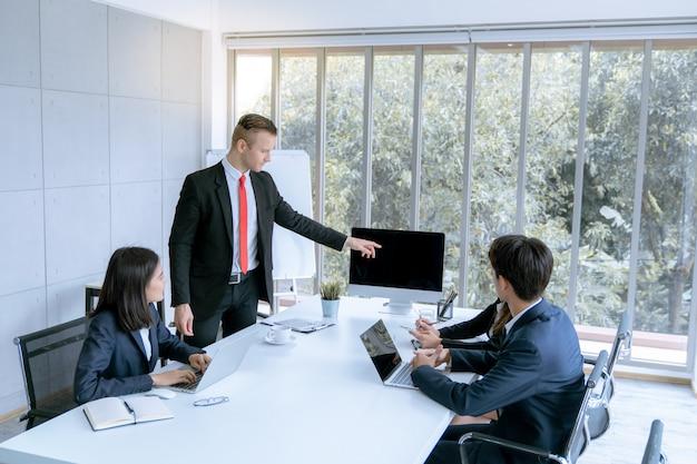 Młodym przedsiębiorcom przedstawiono klientowi projekt pracy marketingowej w biurze pokoju konferencyjnego