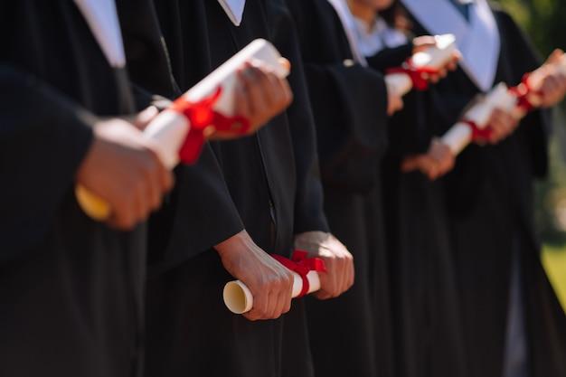 Młodzi absolwenci w sukniach ukończenia szkoły stojących obok siebie