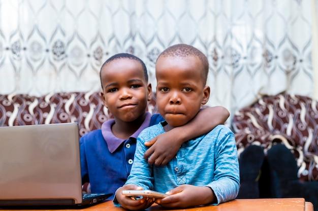 Młodzi afrykańscy bracia uśmiecha się za pomocą technologii, patrząc w kamerę