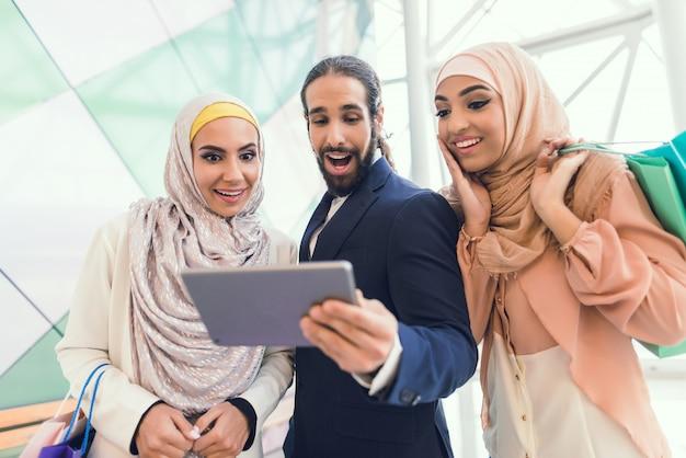 Młodzi arabscy ludzie robi zakupy w nowożytnym centrum handlowym.