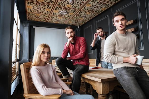 Młodzi atrakcyjni koledzy siedzący i coworking