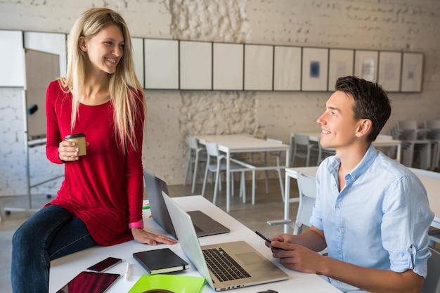 Młodzi atrakcyjni ludzie pracujący razem online w otwartej przestrzeni co-working office room