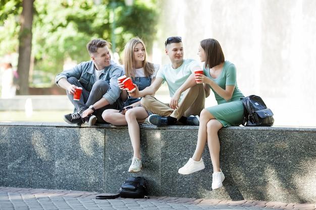Młodzi atrakcyjni ludzie zabawy razem na świeżym powietrzu. ludzie piją kawę i uśmiechają się. grupa przyjaciół idących razem.