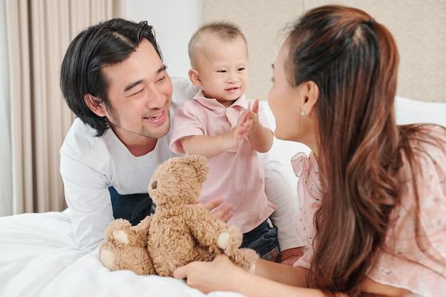 Młodzi azjaci bawią się ze swoim małym dzieckiem podczas odpoczynku na łóżku