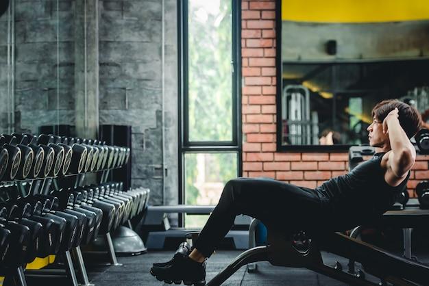Młodzi azjaci ćwiczą w formie ćwiczeń, wzmacniając mięśnie brzucha i wzmacniając brzuch.