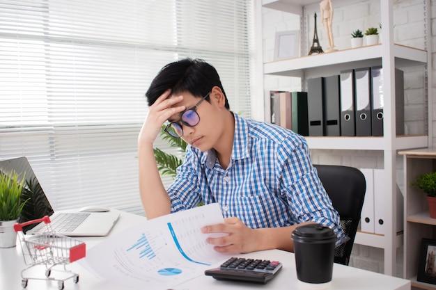 Młodzi azjatyccy biznesmeni są zestresowani pracą w biurze. dłońmi dotknij jego głowy na biurku białym.