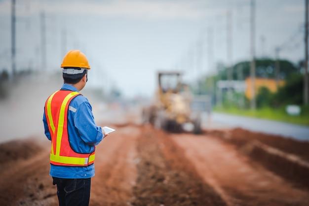 Młodzi azjatyccy inżynierowie nadzorują budowę dróg i kontrolują je na placach budowy.