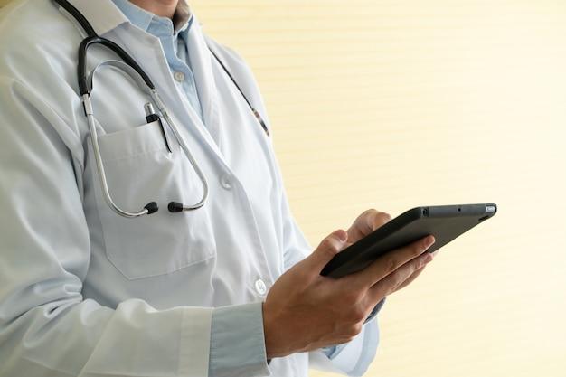Młodzi azjatyccy lekarze używający tabletów do sprawdzania danych i informacji do badania zdrowia pacjentów.