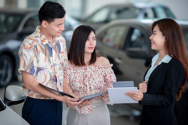 Młodzi azjatyccy miłośnicy chętnie kupują nowy samochód u dealera i kupują samochód u dealera samochodowego.