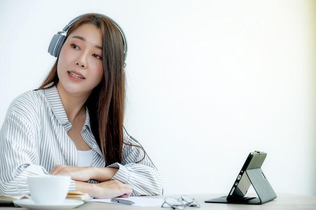 Młodzi azjatyccy nauczyciele uczą przez internet przez internet w swoim domowym biurze
