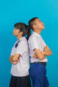 Młodzi azjatyccy studenci i azjatyccy studenci płci męskiej stoją razem na niebiesko.