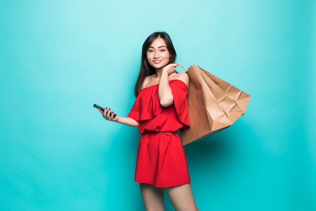 Młodzi azjatykci kobiety przewożenia torba na zakupy i wysylanie sms na telefonie odizolowywającym na zieleni ścianie