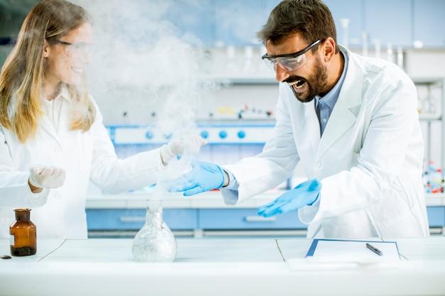 Młodzi badacze przeprowadzają eksperyment z dymem na stole w laboratorium chemicznym