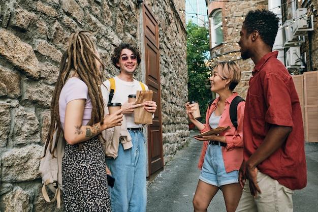 Młodzi beztroscy przyjaciele z napojami stoją przy nowoczesnym budynku