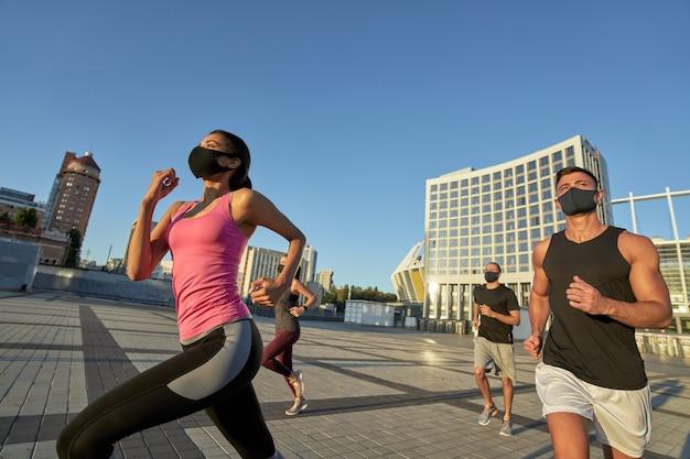 Młodzi biegacze rasy mieszanej w maskach ochronnych