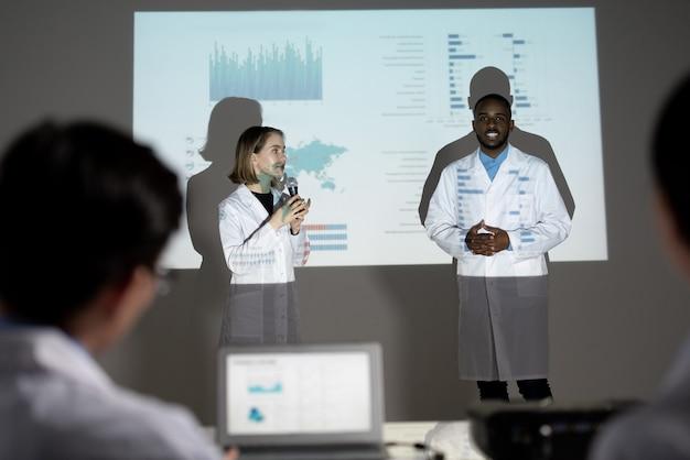 Młodzi biolodzy wieloetniczni stoją przed ekranem projekcyjnym z danymi statystycznymi i opowiadają o idei kampanii ekologicznej na zjeździe
