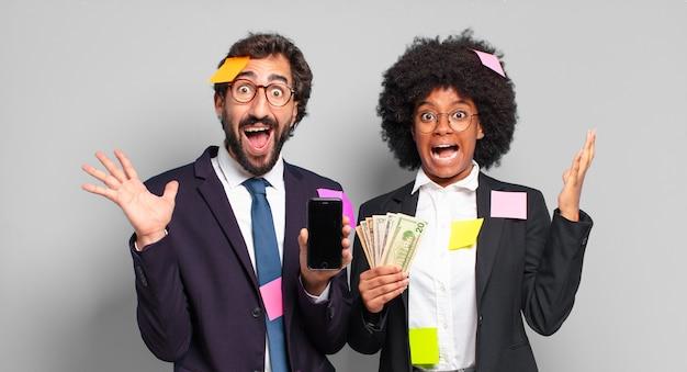 Młodzi biznesmeni czują się szczęśliwi, podekscytowani, zaskoczeni lub zszokowani, uśmiechnięci i zdumieni czymś niewiarygodnym. humorystyczny pomysł na biznes