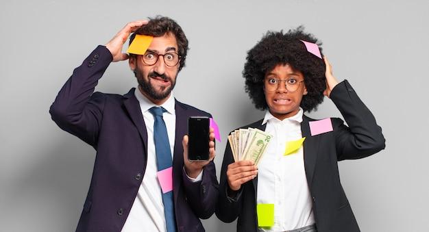 Młodzi biznesmeni czują się zestresowani, zmartwieni, zaniepokojeni lub przestraszeni, z rękami na głowie, panikują przy pomyłce. humorystyczny pomysł na biznes