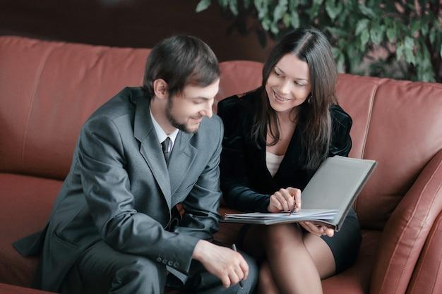 Młodzi biznesmeni omawiają dokument biznesowy siedzący na kanapie w centrum biznesowym