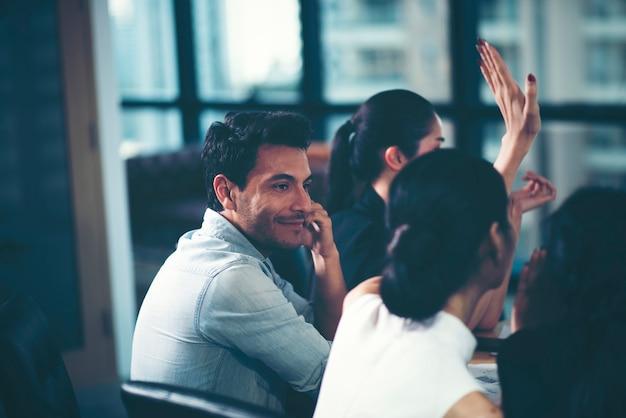 Młodzi biznesmeni patrzą na kolegów podczas spotkania.