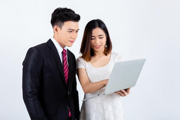 Młodzi biznesmeni pracuje z laptopem na bielu