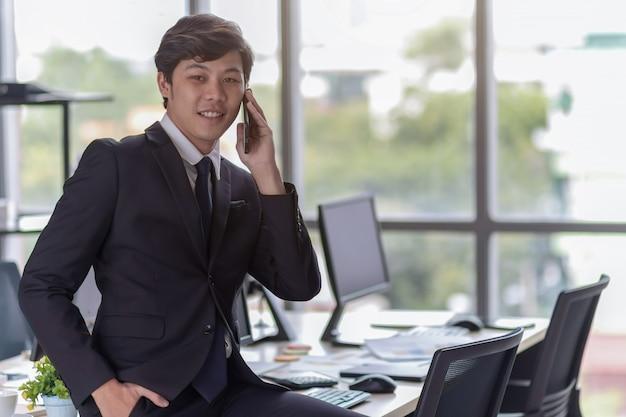 Młodzi biznesmeni rozmawiają przez telefon.