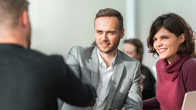 Młodzi biznesmeni, ściskając ręce na spotkaniu w biurze