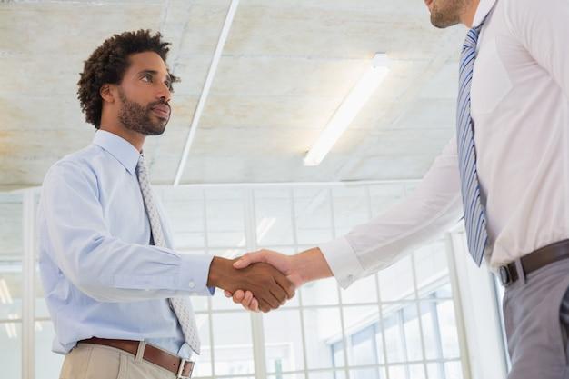 Młodzi biznesmeni trząść ręki w biurze