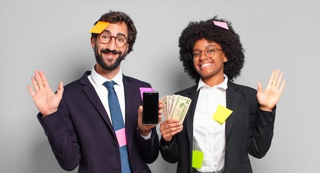 Młodzi biznesmeni uśmiechają się radośnie i wesoło, machają ręką, witają cię i witają lub żegnają