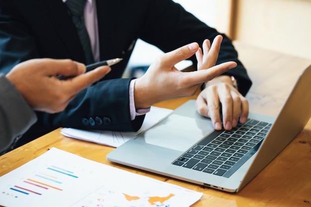 Młodzi biznesmeni za pomocą laptopa na spotkaniu. burza mózgów pomysłów inwestycyjnych planowanie marketingowe projekt i prezentacja finansów.