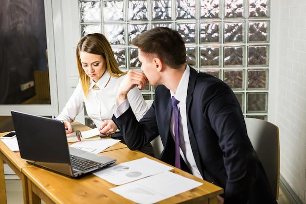 Młodzi biznesowi koledzy dyskutuje pracę na laptopie w coworking przestrzeni, korporacyjni biznesmeni