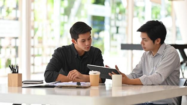 Młodzi biznesowi koledzy opowiada z cyfrową pastylką w nowożytnym biurze.