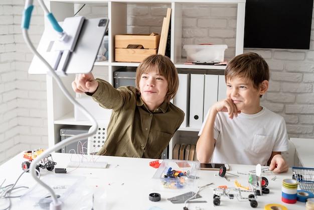 Młodzi chłopcy bawią się robiąc samochody-roboty oglądając program edukacyjny na cyfrowym tablecie, wskazując palcem