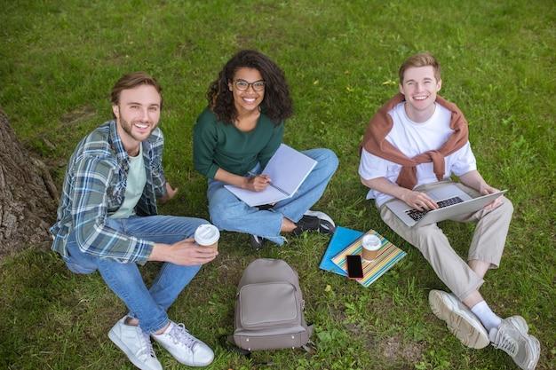 Młodzi chłopcy i dziewczyna siedzą na trawie w pobliżu budynku uczelni