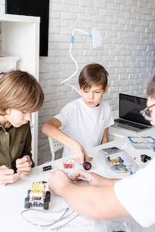 Młodzi chłopcy i nauczyciel bawią się razem konstruując samochody-roboty w warsztacie