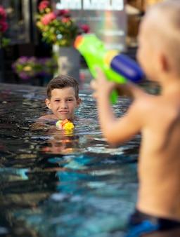 Młodzi chłopcy na basenie z pistoletami na wodę