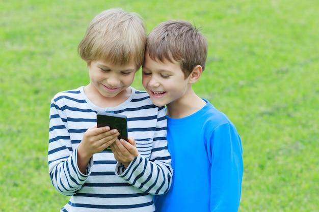 Młodzi chłopcy patrząc na telefon komórkowy