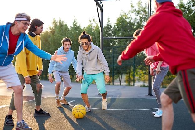 Młodzi chłopcy rasy kaukaskiej mają fantastyczną aktywną grę w koszykówkę