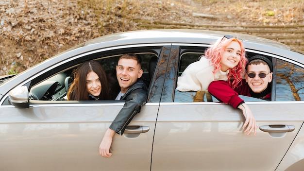 Młodzi człowiecy i kobiety patrzeje z samochodowego okno
