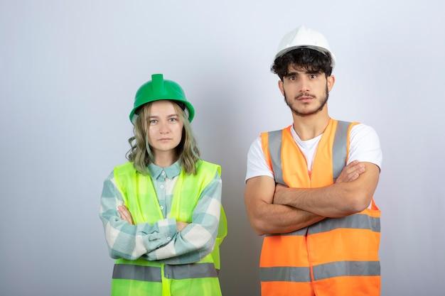Młodzi, dobrze wyglądający inżynierowie w hełmach stojący nad białą ścianą. wysokiej jakości zdjęcie