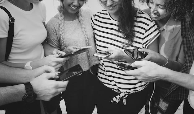 Młodzi dorosli przyjaciele używa smartphones wpólnie outdoors kultury młodzieżowej pojęcie