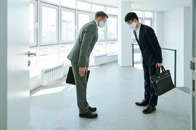 Młodzi eleganccy biznesmeni międzykulturowi z teczkami witają się w ukłonie na spotkaniu w dużym, współczesnym biurze