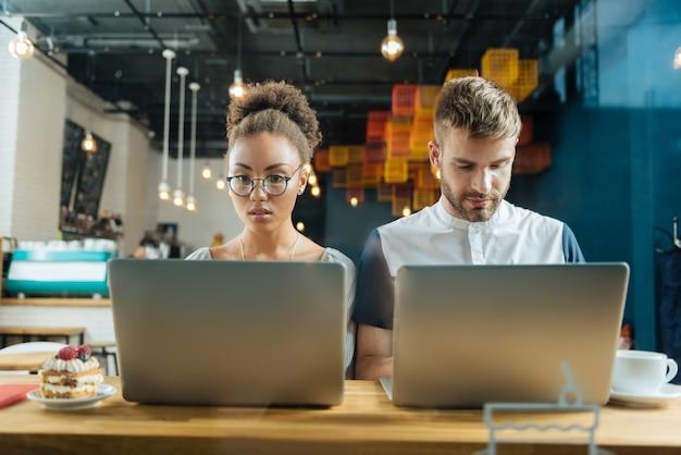 Młodzi freelancerzy. dwóch młodych freelancerów czuje się bardzo zajętych podczas ciężkiej pracy siedząc w kawiarni