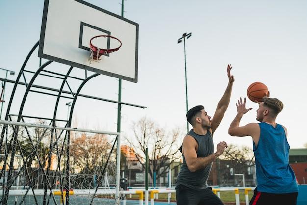 Młodzi gracze koszykówki grający jeden na jednego.