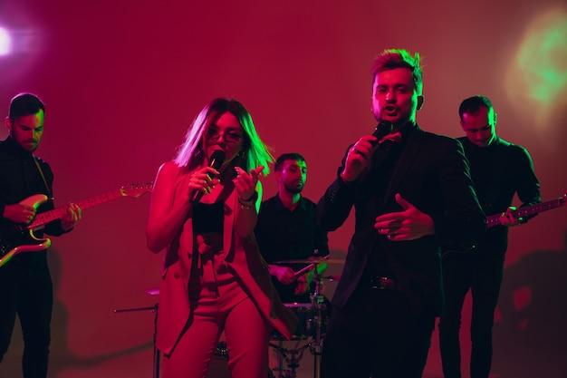 Młodzi i radośni muzycy kaukascy występujący na czerwonym tle studio w świetle neonów. pojęcie muzyki, hobby, festiwalu. kolorowy portret współczesnego artysty. uważny i zainspirowany. sztuka, zespół coverowy.