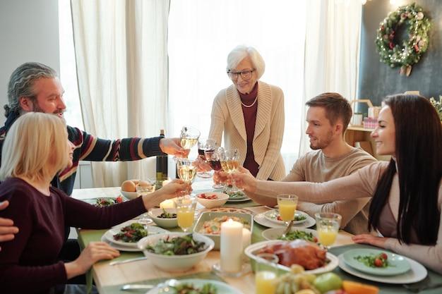 Młodzi i starsi członkowie dużej rodziny brzęczący kieliszkami wina nad świątecznym stołem podczas obiadu dziękczynienia