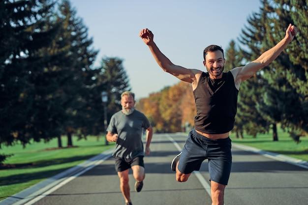 Młodzi i starzy sportowcy biegający po drogach